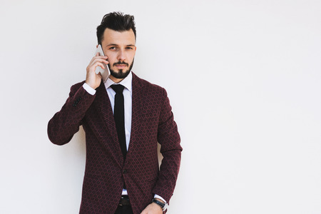 Trendy and fashionable businessman posing on a white background and talking on the phone. Stock Photo