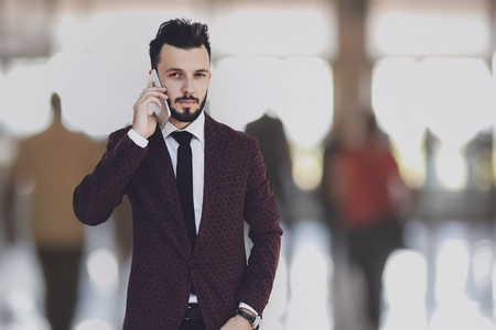 Global communication concept - businessman posing on a blured background of business people and talking on the phone.