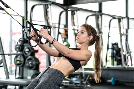 Cute fitness girl doing hard athletic workout in the gym