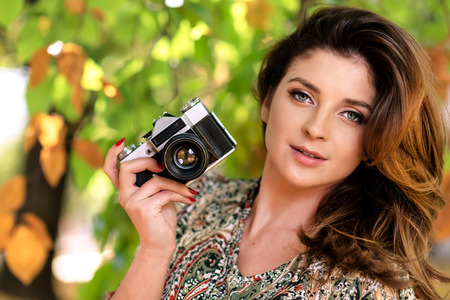 Beautiful and lovely woman holding a retro SLR camera and taking photos in an autumn park on a sunny day Stock Photo
