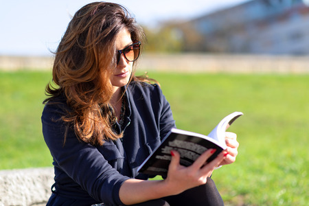 Beautiful young woman with a nice hairstyle and sunglasses sitting outdoor and reading a book on a sunny day.