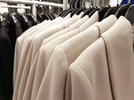 shopping concept image - collection of fashionable clothes hanging in a row in the store ( selective focus) Stock Photo