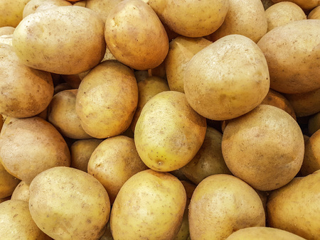 Close-up of a fresh raw potatoes for sale as an agricultural background or texture.