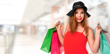 Attractive and young woman in a red dress holds bags in her hands and enjoys shopping in the mall ( copy space)