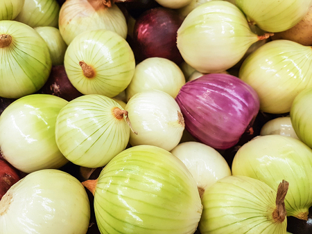 Close-up of a fresh raw onions for sale as an agricultural background or texture.