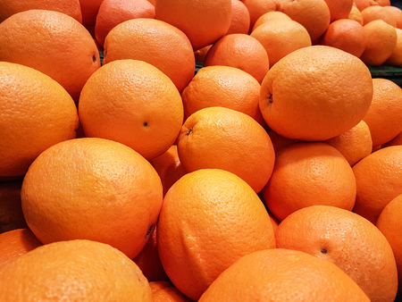 Close-up of a fresh orange fruits for sale as an agricultural background or texture. Stock Photo