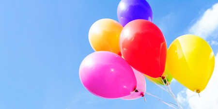 Outdoors party decoration concept - mix of colorful balloons on a blue sky background with copy space. Stock Photo