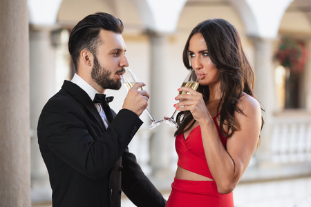 Elegant couple of lovers with a glass of wine or champagne standing on a balcony during luxury party. Stock Photo