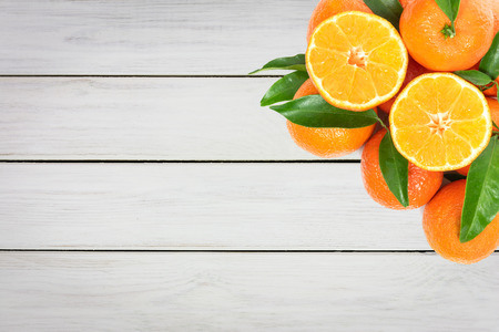 Tropical fruit composition - group of fresh oranges or tangerines  on a wooden vintage table (copy space)