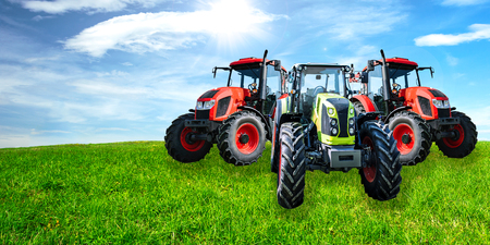 Agricultural advertisement banner - group of new and modern generic tractors on a green meadow in sunny day (mixed).