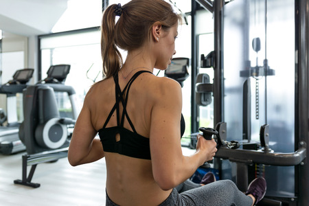 Back view of a fitness woman doing heavy athletic workout in the gym.