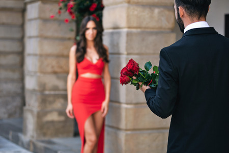 Back view of a man giving a bouquet of red roses to a woman during romantic dating.