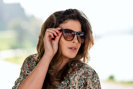 Portrait of a lovely fashion model with sunglasses posing outdoors in the seacoast resort on a sunny day. Stock Photo