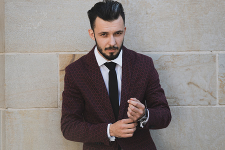 Young and fashionable man buttoning a cuff and posing outdoor on a stone wall background