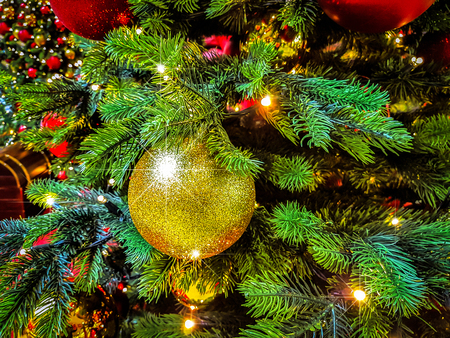 Beautiful Christmas background - shiny baubles on a background of blurred lights on a Christmas tree with bokeh effect. Stock Photo