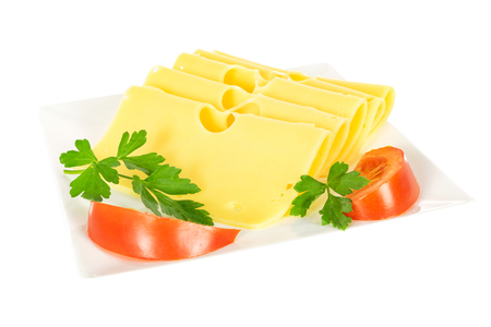 Pieces of fresh yellow cheese with parsley and tomatoes on a plate isolated on a white background in close-up.