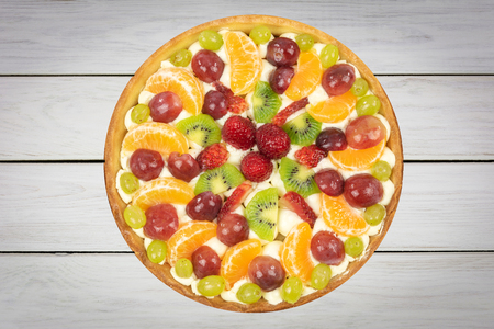 Top view of a fresh homemade multi-fruit tart cake on a wooden old table (high details).