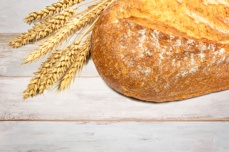 Fresh loaf of bread with wheat grains on a wooden vintage table in close up. Stock Photo
