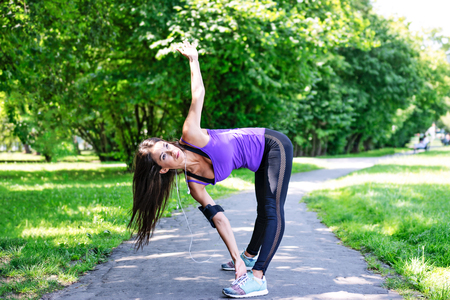 Beautiful young girl stretching before jogging in the park on a sunny morning.