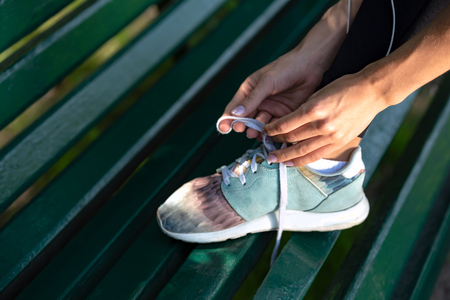 Runner woman tying shoelaces on bench during workout in the park.