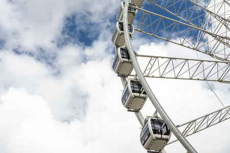 Part of a big ferris wheel on a cloudy sky background with copy space.