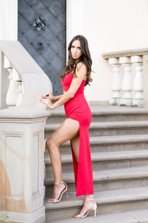 Fashion outdoor photo of beautiful and elegant woman with dark hair in a red dress posing on the stairs. Stock Photo