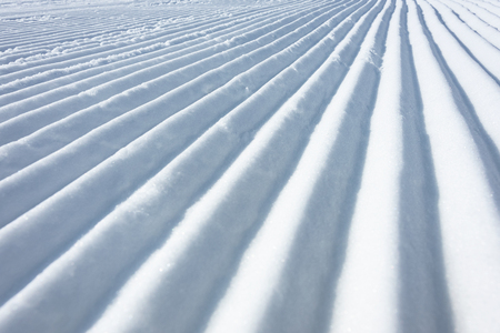 Geometry track lines on a ski slope left by a snowcat as a texture background.