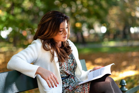 Beautiful young woman sitting on a bench in the park and reading a book on a sunny autumn day. Stock Photo