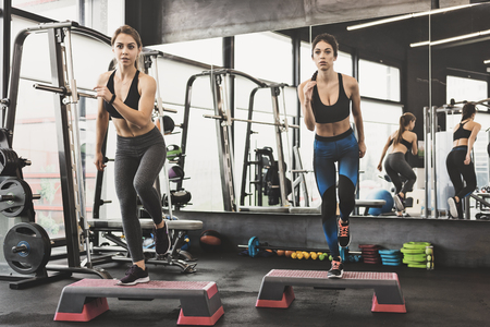 Two fit attractive women doing workout with steppers in the gym