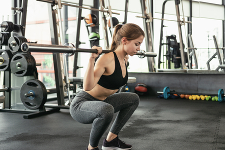 Cute girl has a hard athletic workout in the gym, doing squats with barbells.