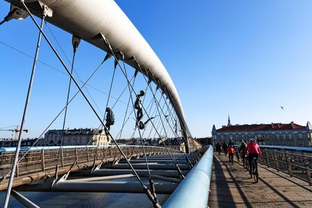 Krakow, Poland - February 16, 2019: People pass through the famous footbridge of Father Bernatka on the Vistula River in Krakow on a sunny day. The footbridge is decorated with acrobatic sculptures by 에디토리얼