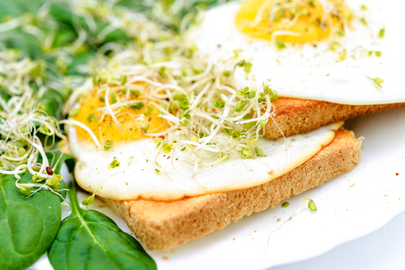 Tasty fried eggs on toast with spinach and young sprouts on a white plate in close-up Stock Photo