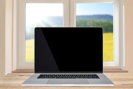 Domestic life template - generic modern laptop with a black screen on a wooden table in the room next to the window (mixed). Stock Photo