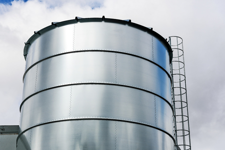 Agriculture Industry equipment - large modern silo for storing grain harvest in close-up.