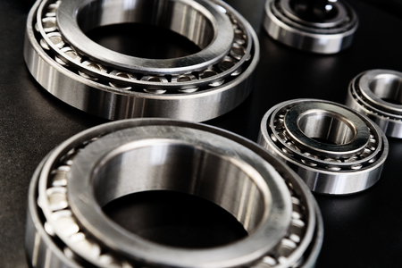 Full frame industrial background - metal bearings in close-up on a black background. Stock Photo