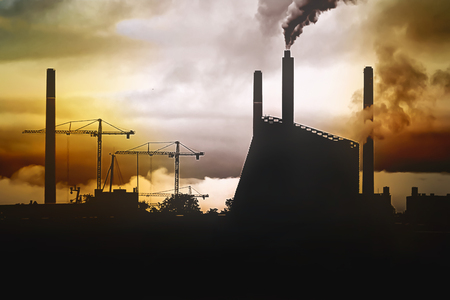 Concept of a polluted environment - a panorama of the city at sunset with the silhouette of a factory and cranes, and smog from chimneys.