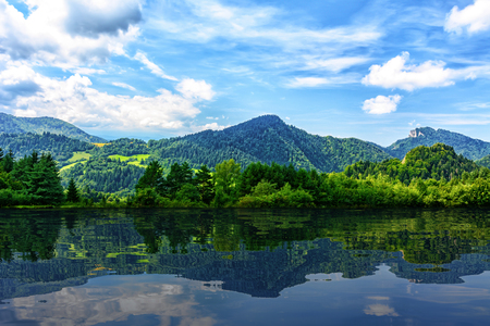 Idyllic panorama of picturesque mountains and blue sky reflected in the lake (mixed)