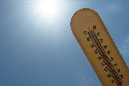 Mercury wooden thermometer shows very high temperature in celsius degree on a sunlight beams background. concept of climate warming changing problem. Reklamní fotografie