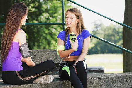 Two fitness young women resting and talking outdoor after workout on a sunny day in the public park (vintage effect)