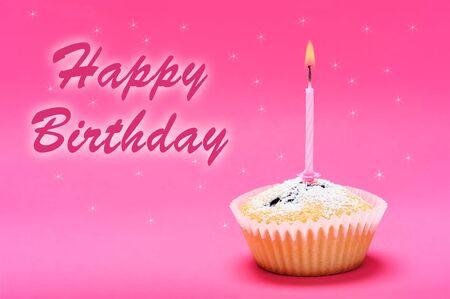 Celebration greetings- single muffin cake with burning candle on a pink background with happy birthday text 스톡 콘텐츠