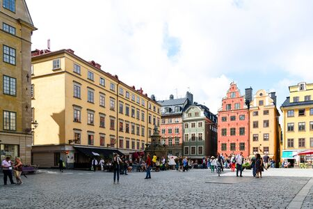 Stockholm, Sweden - August 09, 2019: Colorful facade of historic patrician houses in Stortorget Square in  the Old Town of Stockholm in Sweden with tourists on a summer sunny day.