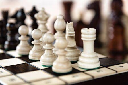 Cerca del tablero de ajedrez con piezas de madera clásicas con enfoque selectivo Foto de archivo