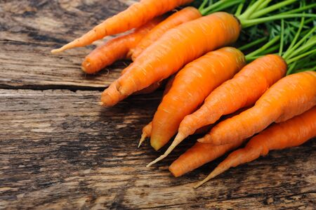 Bunch of fresh organic carrots on a wooden rustic table