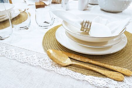 Luxury table setting - golden cutlery and plates with napkin on white tablecloth in close-up Stockfoto - 129804086