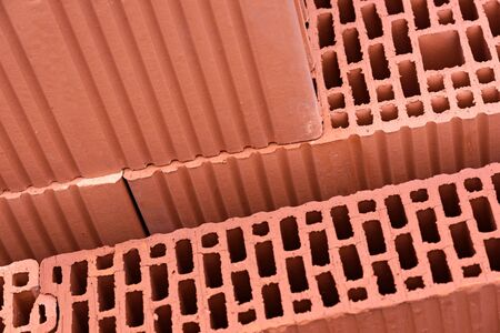 Modern construction industry concept - thermo isolated red bricks for building wall in close-up. Banco de Imagens