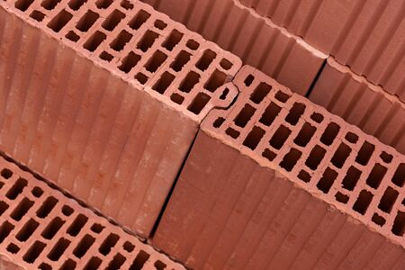 Modern construction industry concept - thermo isolated red bricks for building wall in close-up. 版權商用圖片