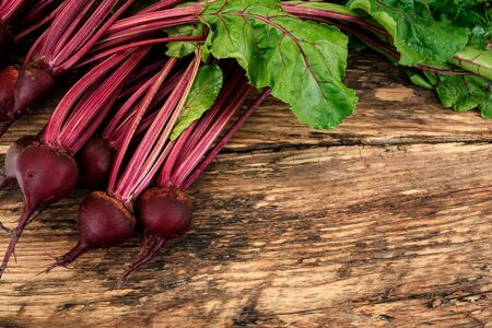 Organic beetroots with herbage green leaves on a rustic wooden table with copy space Imagens