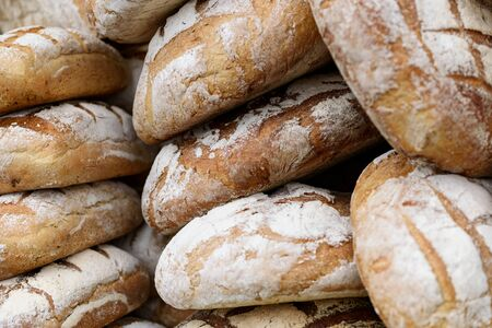 Pile of freshly baked wholemeal breads in the bakery or local farmer market.