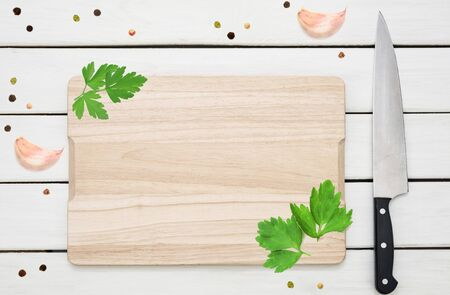 Rustic culinary template - top view of an empty cutting board with spices ( garlic, pepper, parsley) and knife on a white wooden table.