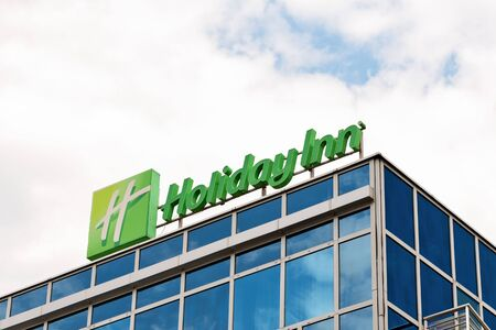 Krakow, Poland - July 12, 2019: Holiday Inn Sign against a cloudy blue sky. Holiday Inn is The American hotel chain and it is owned by InterContinental Hotels Group. Editorial